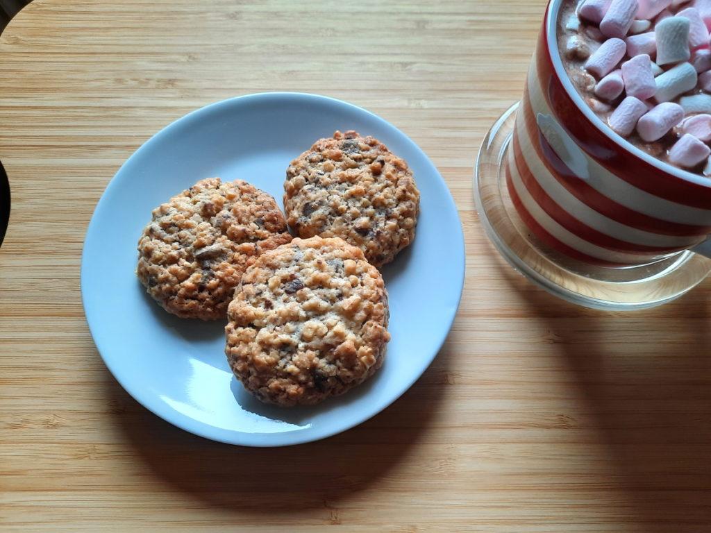 Kleiner weißer Teller mit drei Kekse, am rechten Rand ist eine gestreifte Tasse mit Kakao zu erahnen