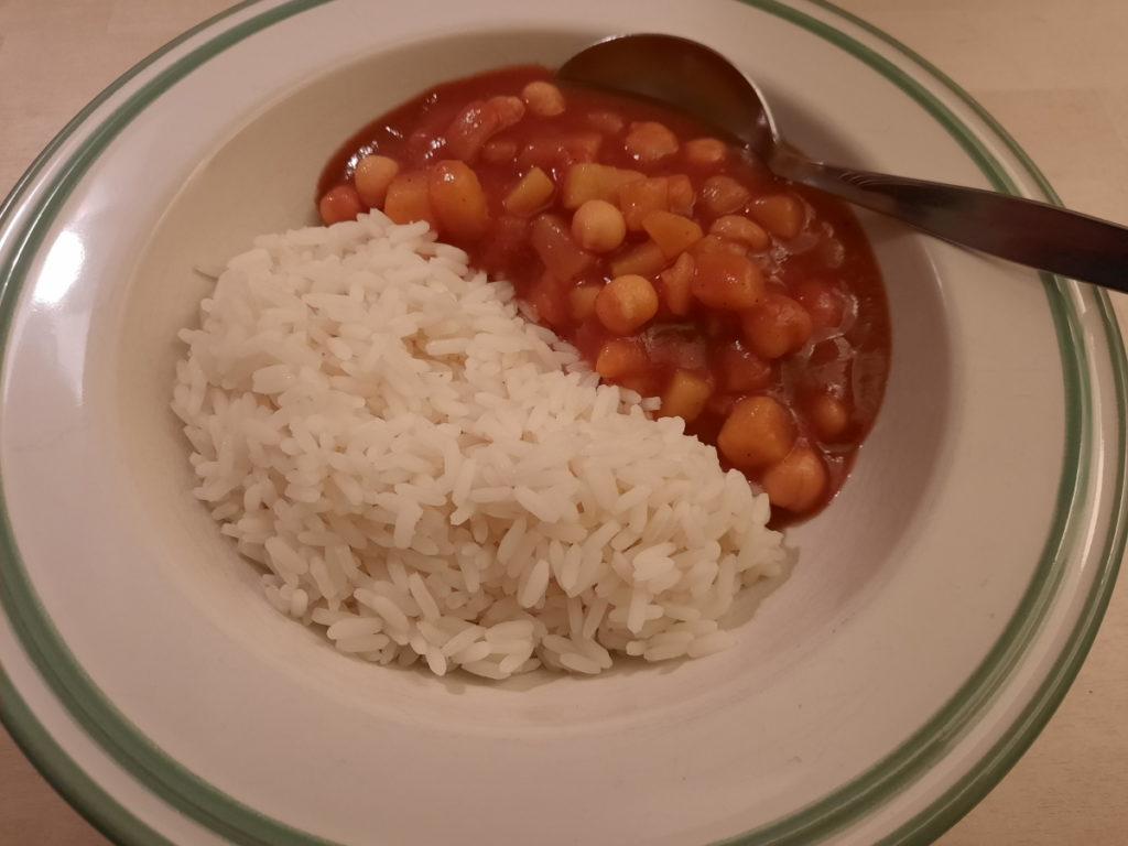 Das Foto zeigt einen Teller, der zur Hälfte mit Reis und zur anderen Hälfte mit einem tomatigen Kichererbsen-Kartoffel-Curry gefüllt ist.