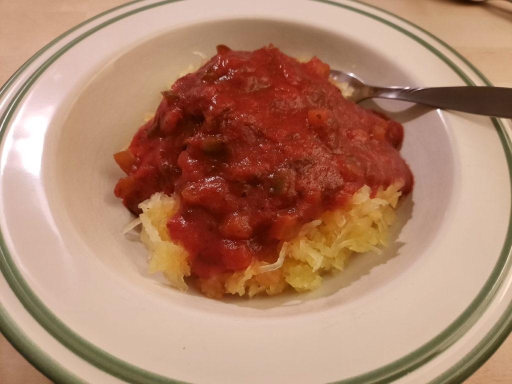 Ein Teller mit Spaghettikürbis und Tomatensauce