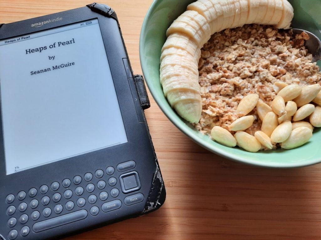 """Eine Schüssel mit Porridge und ein eReader, dessen Display den Titel """"Heaps of Pearl"""" zeigt"""