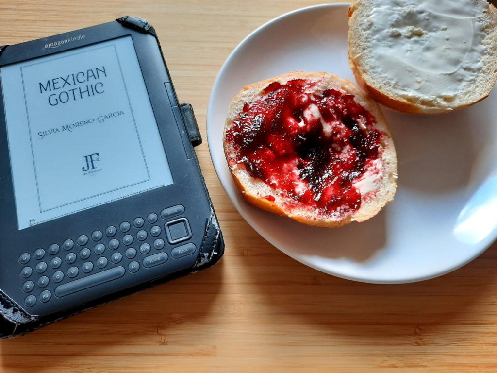 Das Foto zeigt einen eReader neben einem Teller mit zwei beschmierten Brötchenhälften
