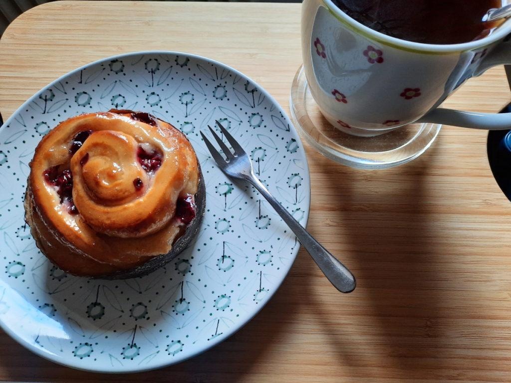 Das Foto zeigt einen kleines Stück Gebäck und eine große Tasse Tee