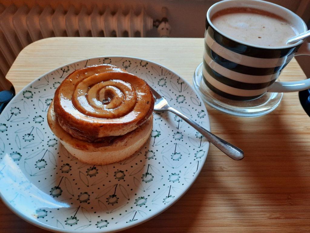 Ein Teller mit einem kleinen Zimtkuchen und daneben eine Tasse mit Kakao