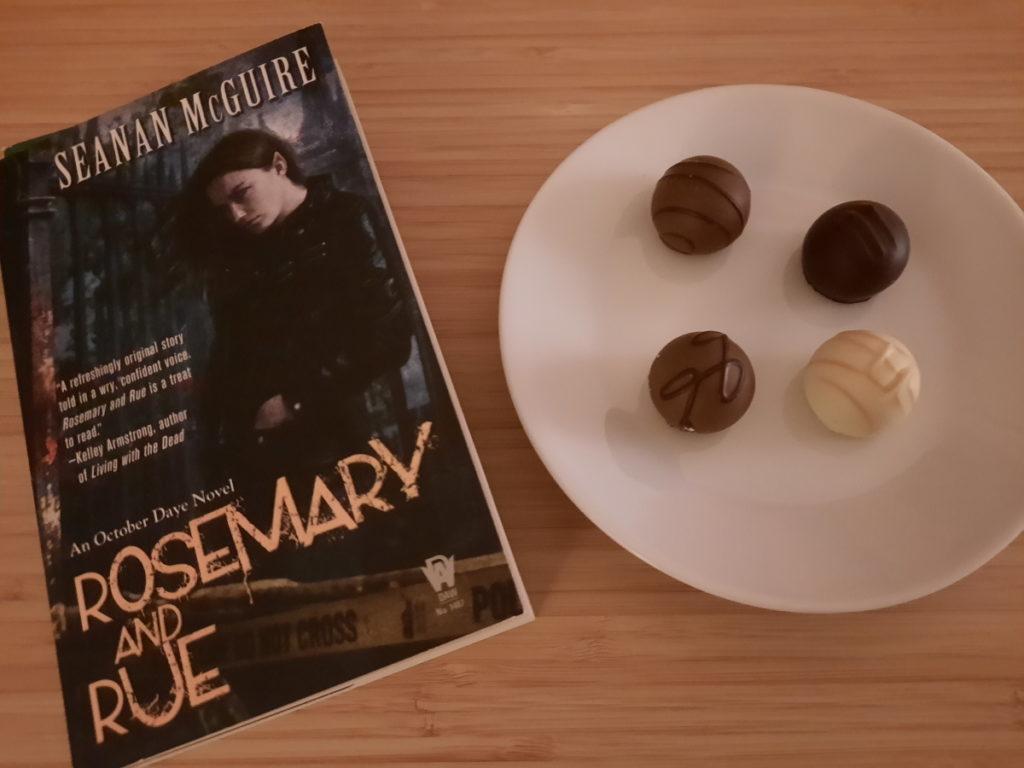 """Ein Foto der Taschenbuchausgabe von """"Rosemary and Rue"""" und von dem daneben stehendem kleinen Teller mit vier Pralinen."""