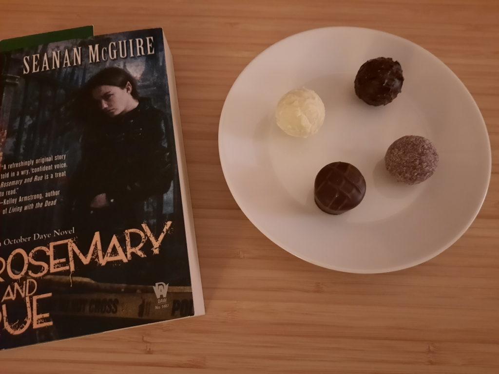 """Auf dem Foto sind die Taschenbuchausgabe von """"Rosemary und Rue"""" und ein kleiner Teller mit vier Pralinen zu sehen."""