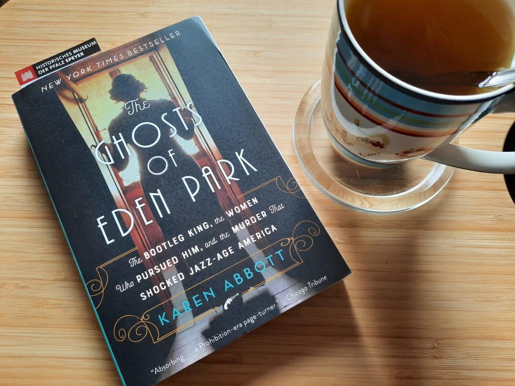"""Ein Foto der Taschenbuchausgabe von """"The Ghosts of Eden Park"""" und daneben eine Tasse Pfefferminztee"""