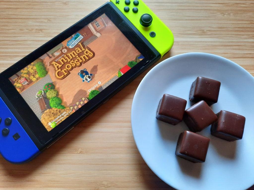 Eine Switch, auf der der Animal-Crossing-Startschirm zu sehen ist, und ein Teller mit fünf Dominosteinen.