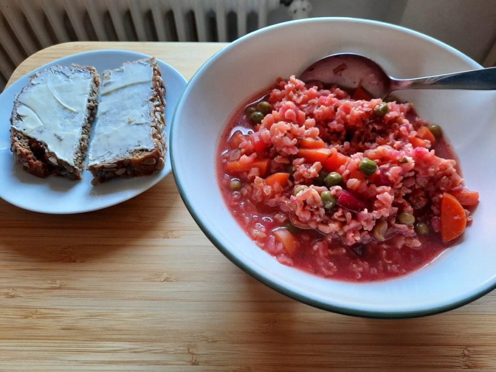 Eine Schale mit Rote-Beete-Möhren-Erbsen-Naturreis-Suppe und daneben ein kleiner Teller mit einem Butterbrot.