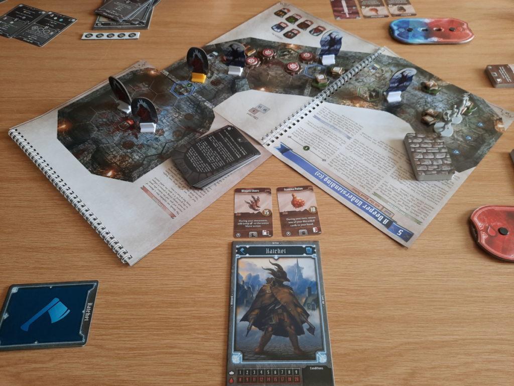 """Ein Brettspielaufbau, wobei das """"Brett"""" aus zwei nebeneinanderliegenden Ringbüchern besteht und davor sieht man einen Charakterbogen und Aktionskarten auf dem Tisch liegen."""