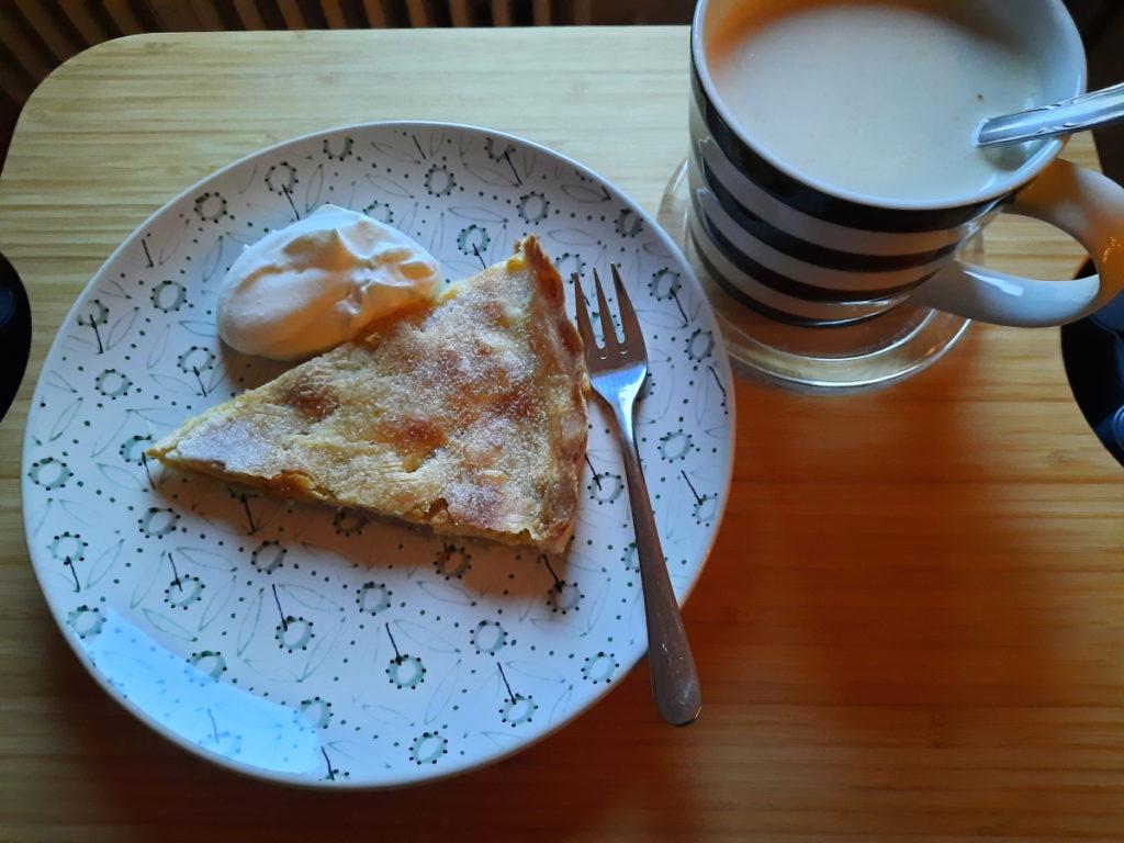 Ein grün gemusterter Teller mit einem sehr flachen Stück Apple Pie und einem Klecks Sahne darauf, daneben eine schwarz-weiß-geringelte Tasse mit Milchkaffee