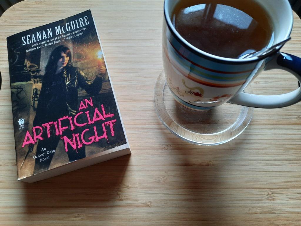 """Das Foto zeigt eine Tasse mit Kräutertee, neben der die Taschenbuchausgabe von """"An Atrificial Night"""" liegt."""