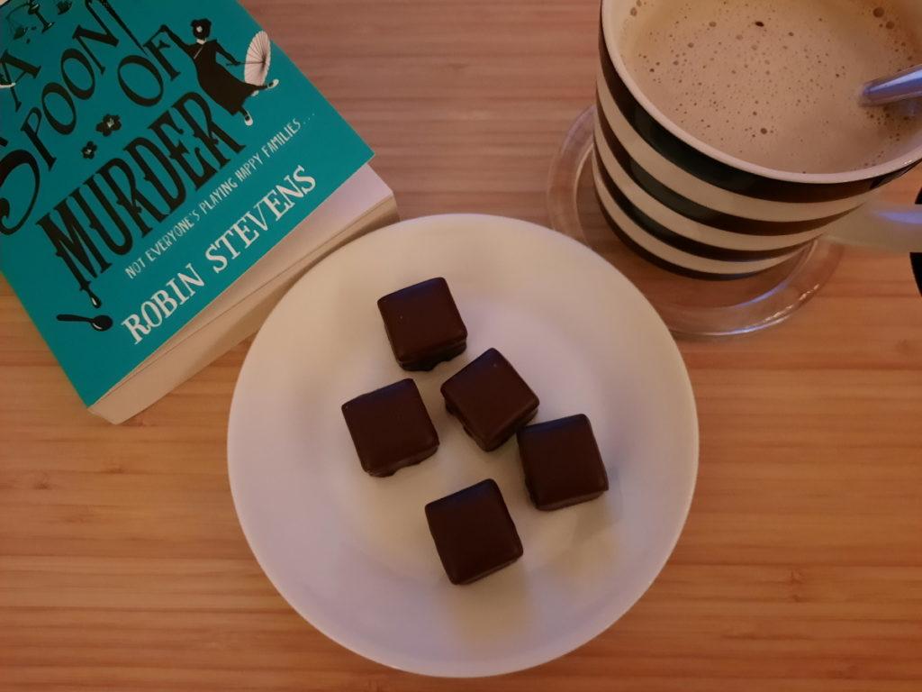 """Eine Untertasse mit fünf Dominosteinen, eine gestreifte Tasse mit Milchkaffee und eine Ecke von """"A Spoonful of Murder"""""""