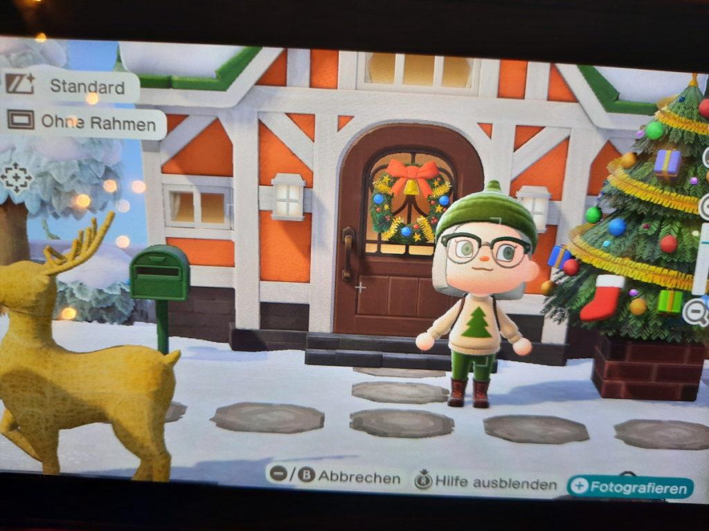 Animal-Crossing-Screenshot mit meiner Spielfigur vor einem Haus mit Weihnachtstürkranz, Weihnachtsbaum und beleuchtetem Rentier