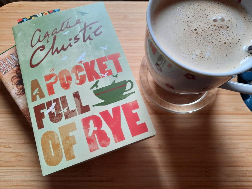 """Das Foto zeigt links zwei aufeinanderliegende Bücher, von denen das obere den Titel """"A Pocket Full of Rye"""" trägt und daneben eine große Tasse mit Milchkaffee"""