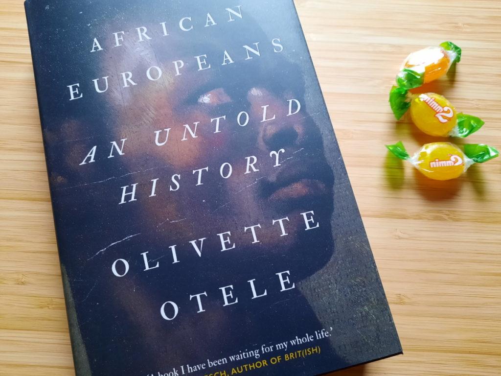 """Eine Hardcover-Ausgabe von """"African European - An Untold History"""" und rechts daneben drei Bonbons."""