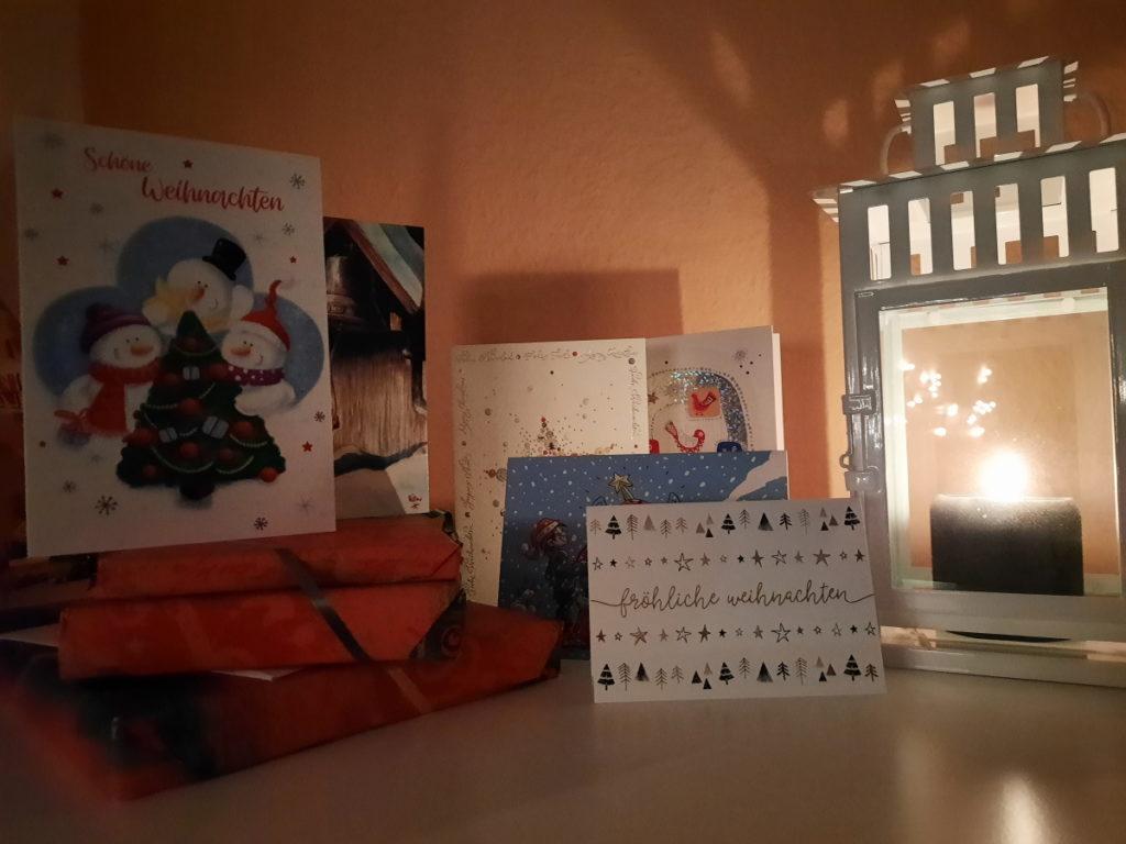 Das Foto zeigt eine brennende Kerze in einer Sturmlaterne (rechts), drei in Weihnachtsgeschenkpapier eingepackte Bücher (links) und einige Weihnachtskarten mit unteschiedlichen Motiven, die dazwischen arrangiert sind.