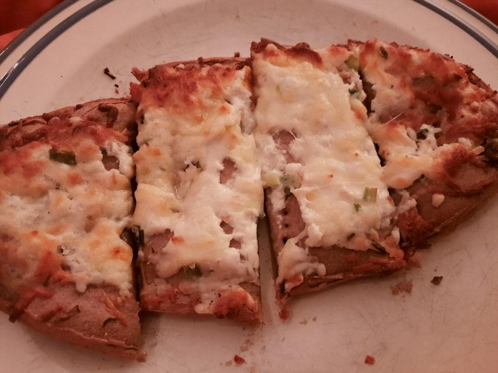 Ein weißer Teller mit einer in vier Teile zerschnittenen Teigscheibe, die mit Käse überbacken wurde.
