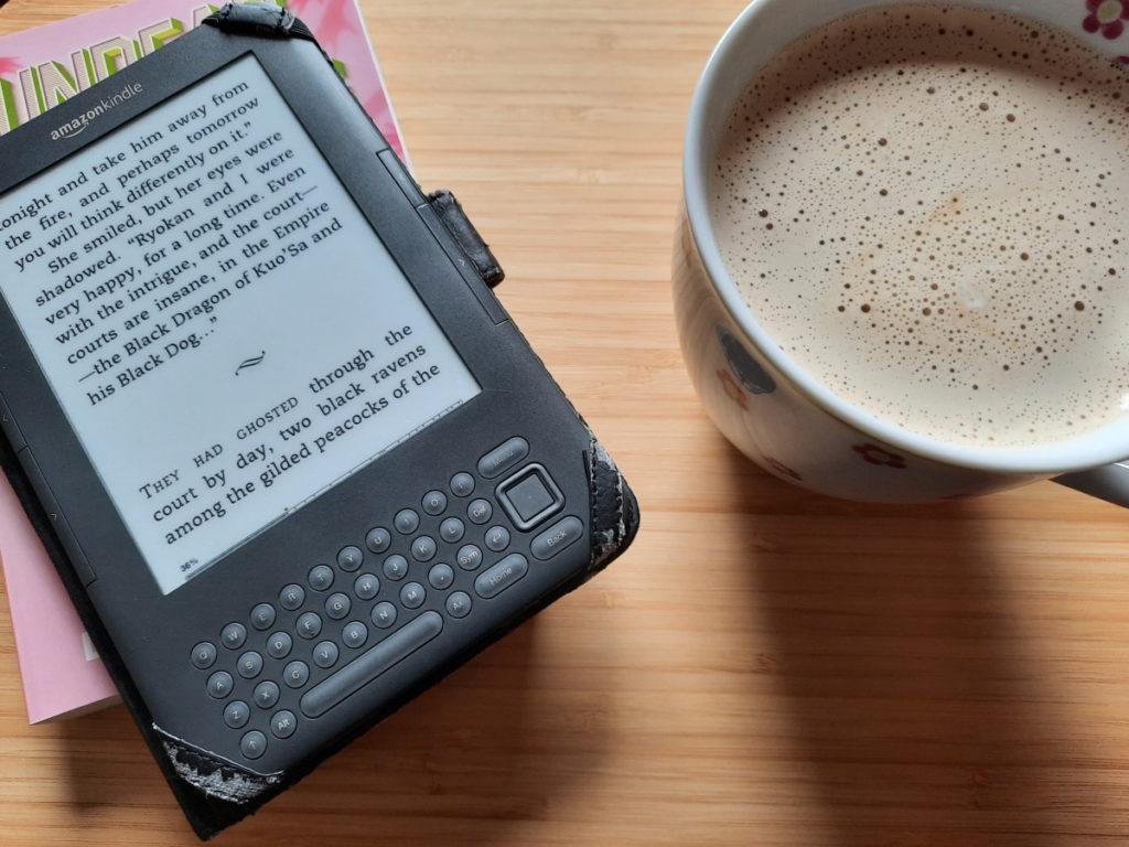 """Das Foto zeigt meinen angeschalteten eReader mit einem Textausschnitt aus """"The Mountain of Iron"""" und daneben steht eine große Tasse mit Milchkaffee"""