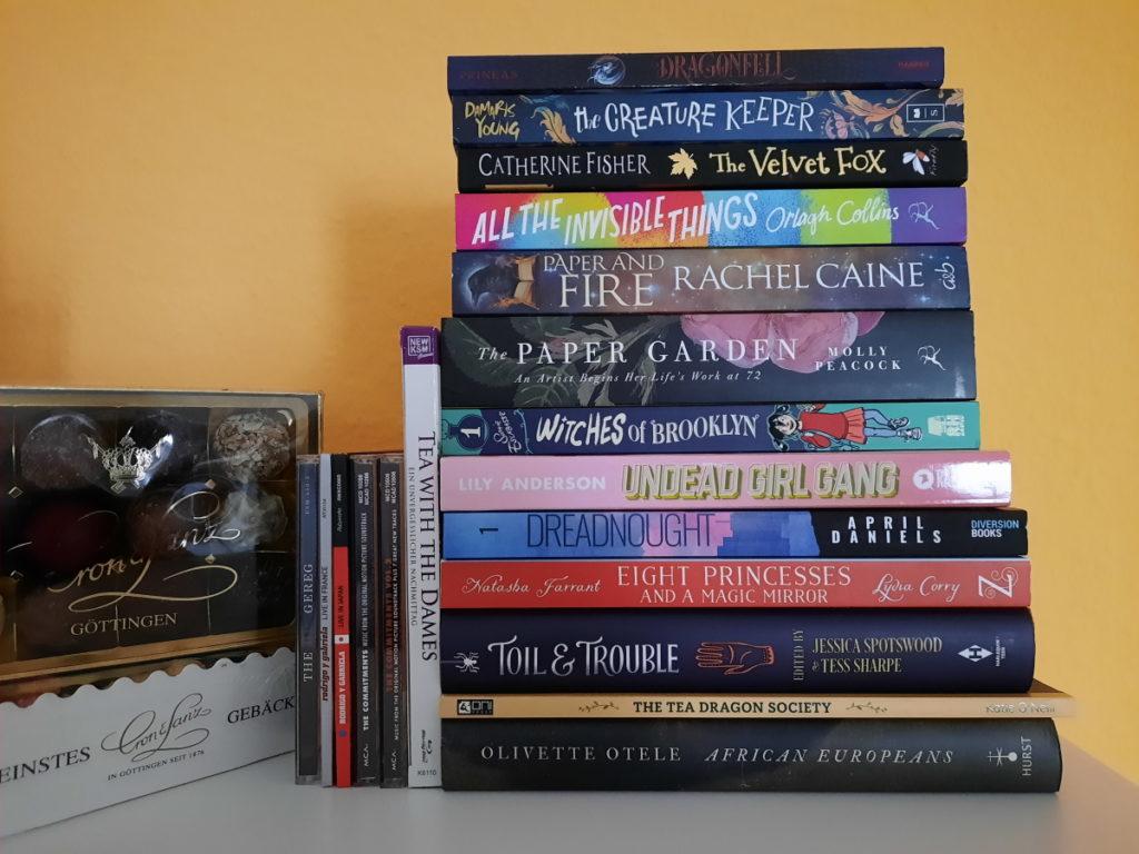 Ein Buchstapel bestehend aus dreizehn Büchern, daneben eine Blu-ray, fünf CDs und drei Packungen mit Pralinen
