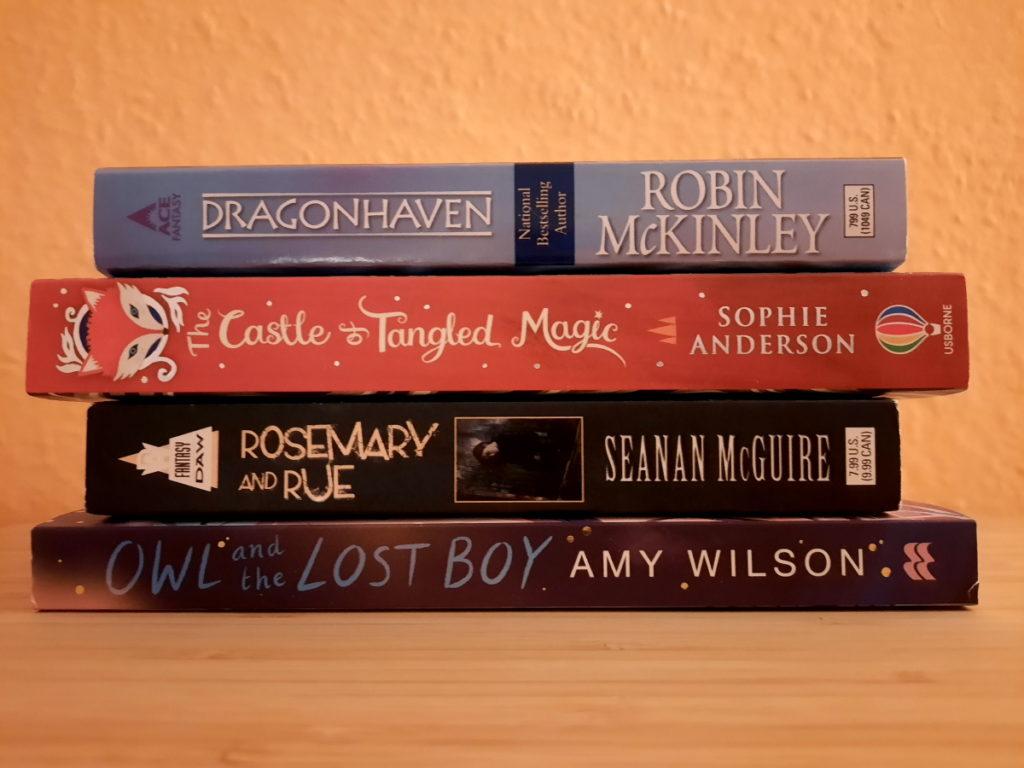 Ein Stapel mit vier Büchern vor einer orangen Wand