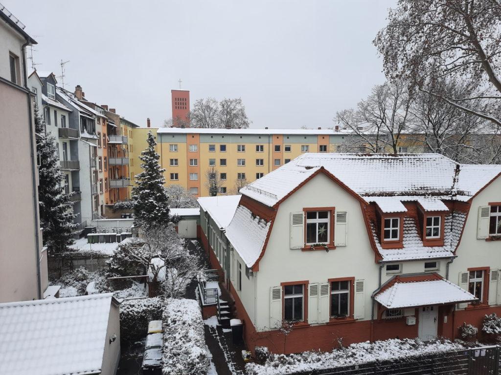 Blick aus dem Fenster auf einen verschneiten U-förmigen Wohnblock der ein altmodisch verschachteltes Häuschen umschließt