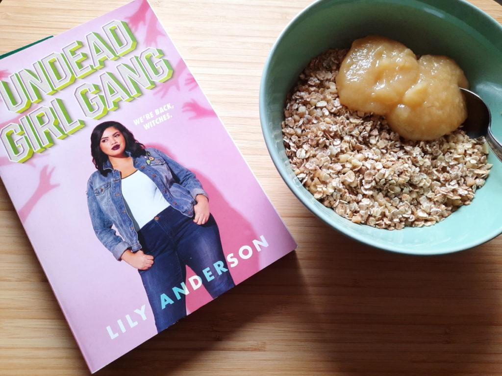 """Links auf dem Foto ist die Taschenbuch-Ausgabe von """"Undead Girl Gang"""" zu sehen, daneben steht auf der rechten Seite eine grüne Schale mit Porridge und etwas Apfelmus."""