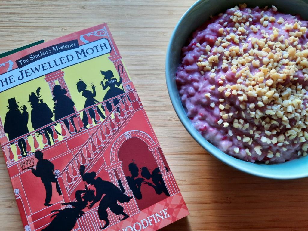 """Noch einmal die Taschenbuchausgabe von """"The Jewelled Moth"""" und daneben eine zartgrüne Schale mit Himbeer-Milchreis, über den ich ein paar gehackte Mandeln gestreut habe."""