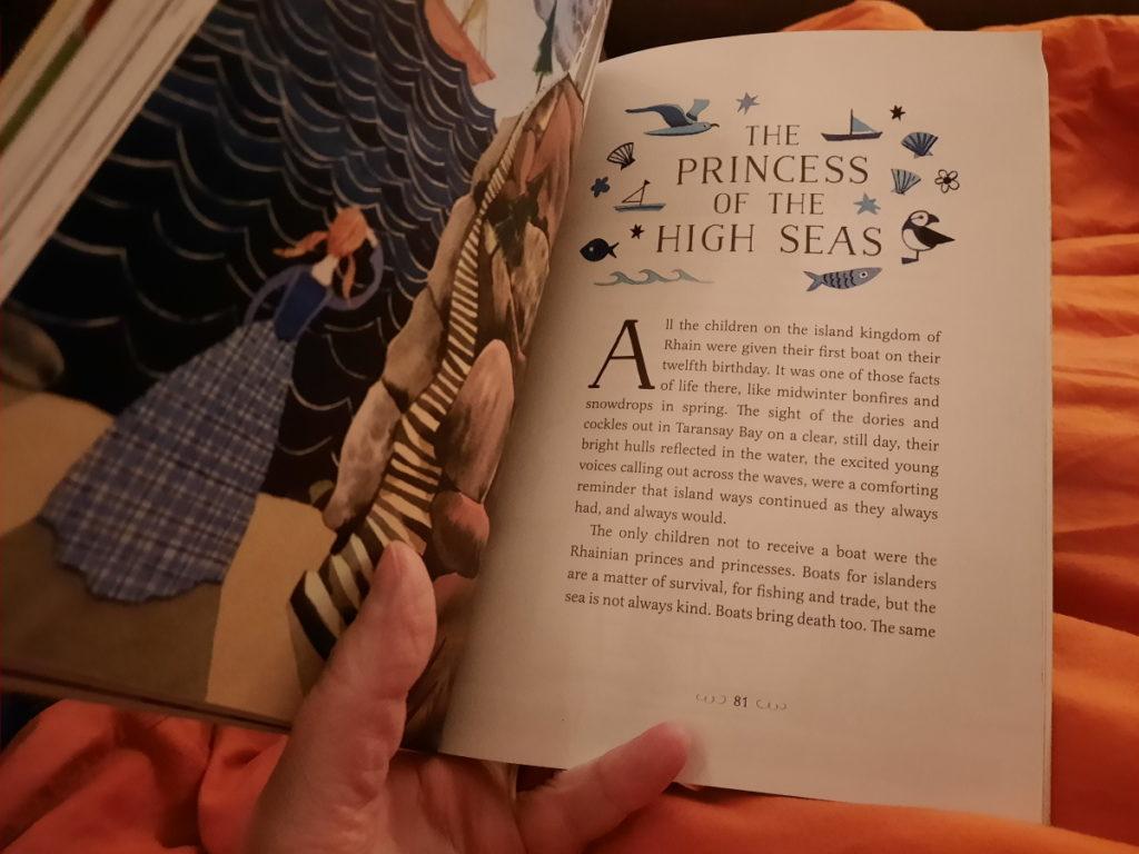 """Auf dem Foto ist ein aufgeschlagenes Buch vor einer orangen Bettdecke zu sehen. Auf der linken Seite des Buches ist eine Illustration mit einer Figur mit hellen Zöpfen und einem blauen Kleid, die dem Betrachter den Rücken zuwendet und auf ein Schiff auf dem Meer hinausblickt, auf der rechten Seite sieht man den Titel einer Geschichte (""""The Princess of the High Seas""""), um den verschiedenen kleine blaue Zeichnungen (Möwe, Fisch, Papageientaucher, Boote und Muscheln) arrangiert sind."""