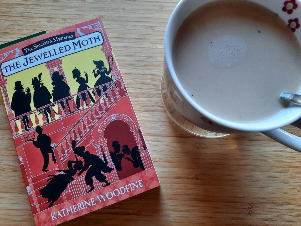 """Ein weiteres Foto mit der Taschenbuchausgabe von """"The Jewelled Moth"""" - dieses Mal steht auf der rechten Seite eine große Tasse mit Milchkaffee"""