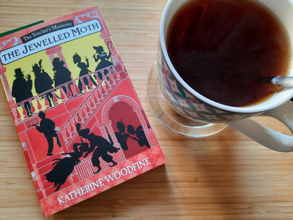 """Das Foto zeigt die Taschenbuchausgabe von """"The Jewelled Moth"""" vn Katherine Woodfinde (schönes Cover mit Scherenschnittartigem Motiv) und daneben eine große Tasse mit schwarzem Tee."""