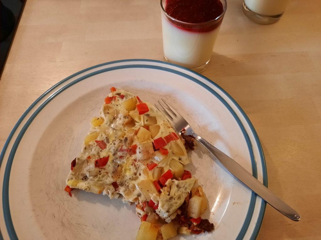 Ein Teller mit einem Viertelstück Kartoffel-Paprika-Frittata und ein Glas, das mit Vanillepudding und Himbeersauce gefüllt ist.