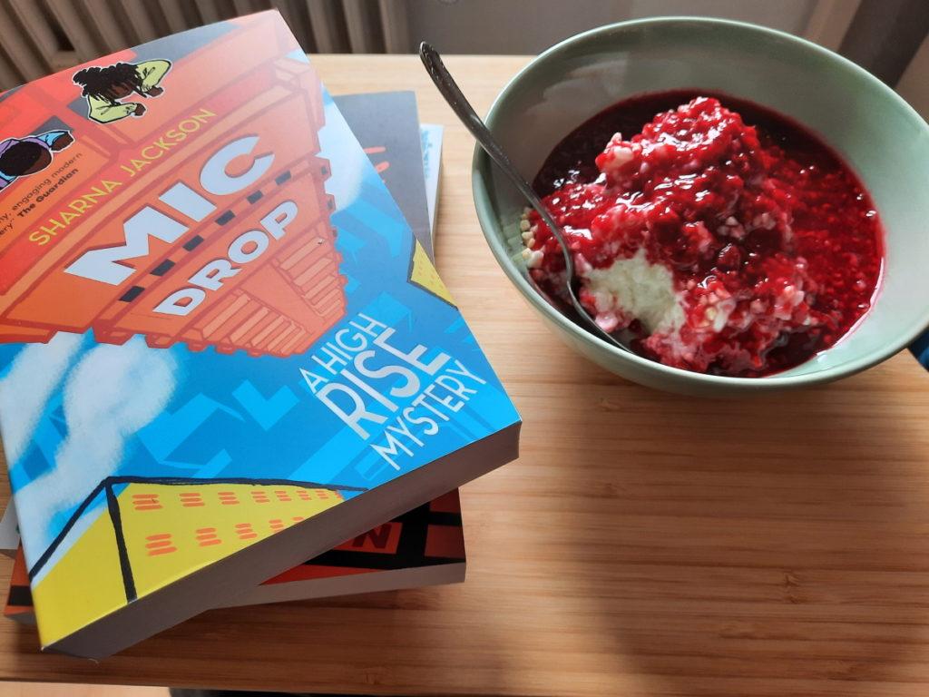 """Ein Stapel aus drei Taschenbüchern, der oberste Titel lautet """"Mic Drop"""" von der Autorin Sharna Jackson. Rechts vom Bücherstapel steht eine zartgrüne Schale mit einer Portion Milchreis, die mit Himbeersauce übergossen würde."""
