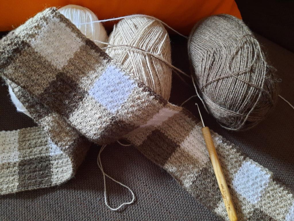 Ein gehäkelter Streifen, der ein Muster aus dunkelbrauner, mittelbrauner und weißer Wolle zeigt, das so ausschaut, als ob die drei Farben miteinander verwebt wären. Drei Wollknäule und eine Häkelnadel.