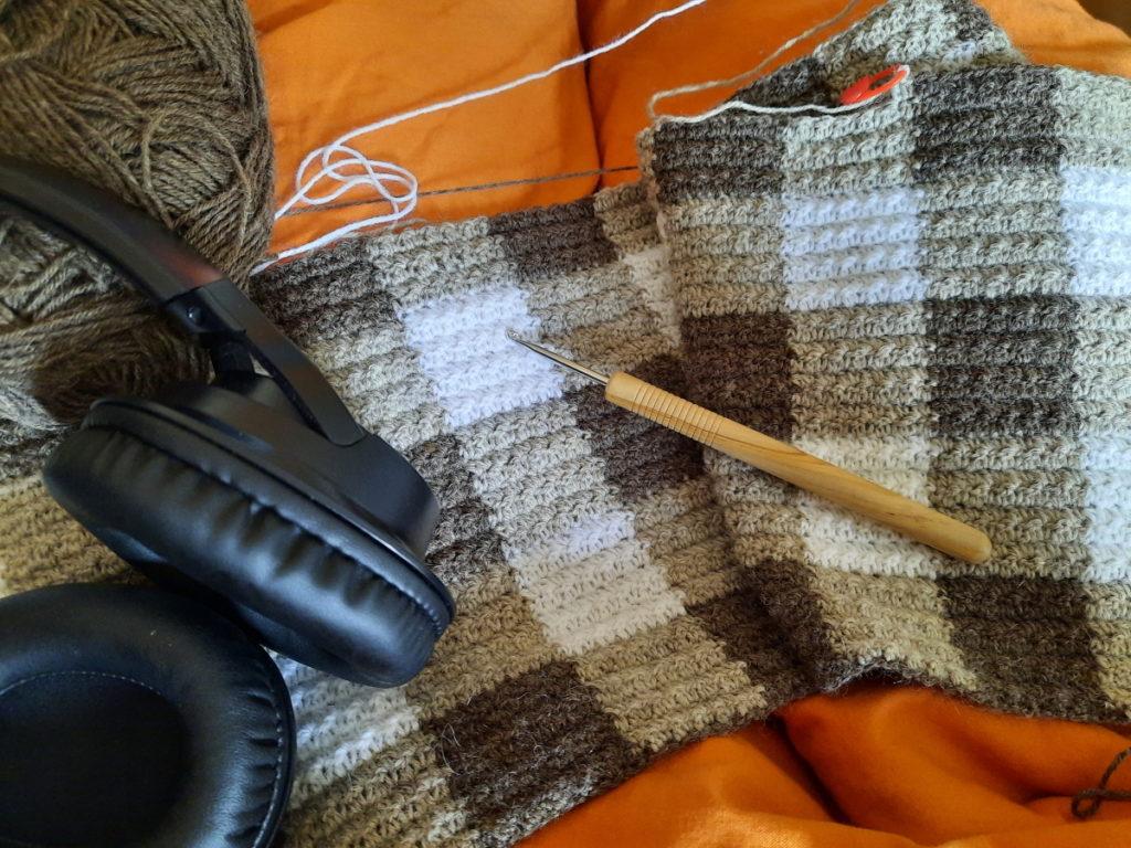Der Anfang einer gehäkelten Decke (man sieht 4 1/2 Reihen eines Karomusters), auf der eine Häkelnadel liegt. Im linken Bildbereich kann man ein dunkelbraunes Wollknäuel erahnen, an den ein Kopfhörer angelehnt wurde.