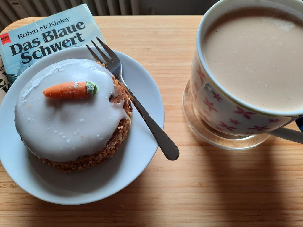 """Ein Stück Karotten-Kuchen auf einem Teller, der auf einem kleinen Bücherstapel steht. Bei dem obersten Buch kann man noch den Titel """"Das Blaue Schwert"""" lesen. Neben dem Stapel steht eine große Tasse mit Milchkaffee."""