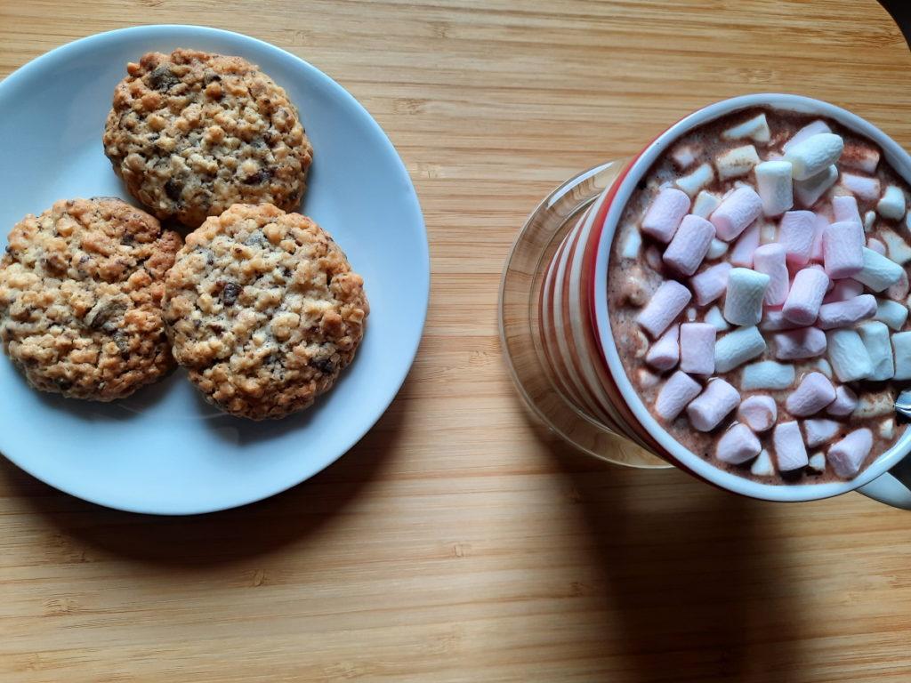 Ein weißer Unterteller mit drei goldbraunen Schokosplitter-Haferflocken-Mandel-Keksen, rechts sieht man eine gestreifte Tasse mit Kakao und einer großen Menge Mini-Marshmallows darauf