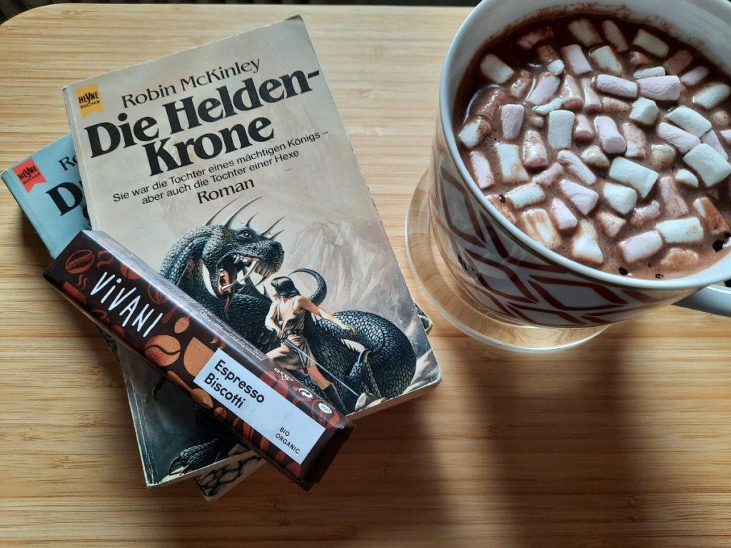"""Links ist die Taschenbuchausgabe von """"Die Helden-Krone"""" zu sehen, auf der ein eingepackter Riegel mit Espresso-Biscotti-Schokolade liegt, rechts davon steht eine große Tasse mit Kakao und Mini-Marshmallows."""