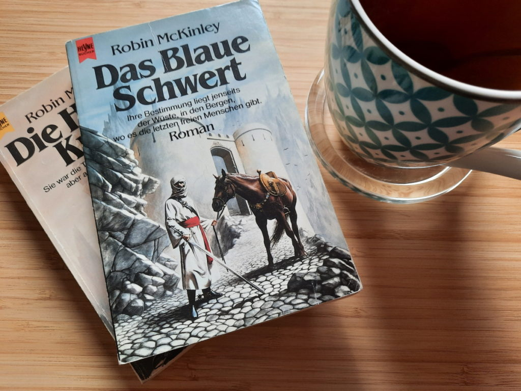 """Zwei aufeinander gestaplete Bücher, bei dem oberen kann man den Titel """"Das Blaue Schwert"""" lesen und daneben steht eine große Tasse mit Pfefferminztee."""