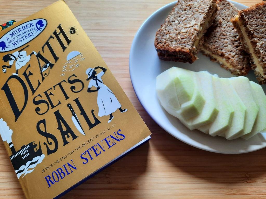 """Links ist eine Ecke von """"Death Sets Sail"""" zu sehen, auf der rechten Seite steht ein weißer Teller mit einer aufgeschnittenen Kohlrabi und einer zusammengeklappten Scheibe Vollkornbrot mit Käse."""