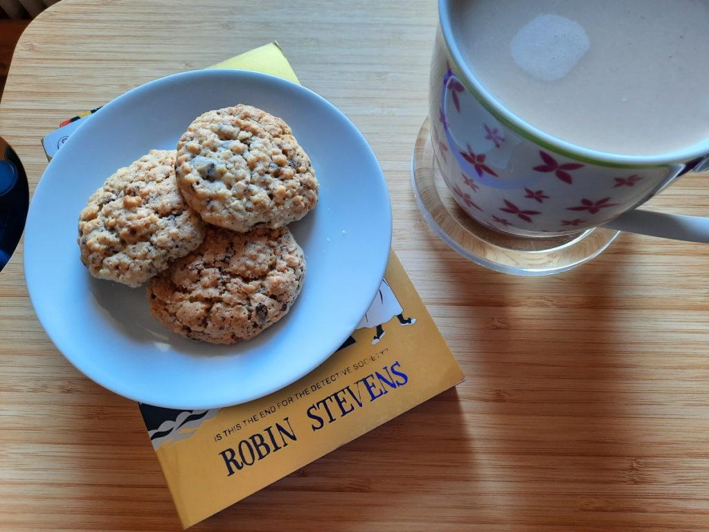 """Ein kleiner Teller mit drei Schoko-Haferflocken-Keksen steht auf """"Death Sets Sail"""" und verdeckt das Cover fast vollständig. Rechts von dem Teller steht eine große Tasse it Milchkaffee."""