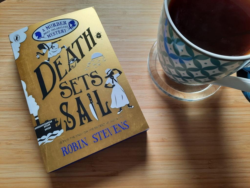 """Die - auf einem Holzbrett liegende - Taschenbuchausgabe von """"Death sets Sail"""" von Robin Stevens (mit einem gold-glänzendem Cover) und rechts daneben eine grün-weiß-gemusterte Tasse mit schwarzem Tee."""