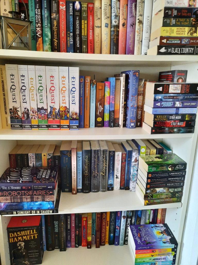 Ein Bücherregal mit alphabetisch geordneten Büchern (und ein paar Comics). Es gibt nur noch drei kleine Stapel vor den Buchreihen und diese bestehen aus kleinen US-Masspaperbacks, die da auch genügend Platz haben, um nicht aus dem Regal zu ragen.