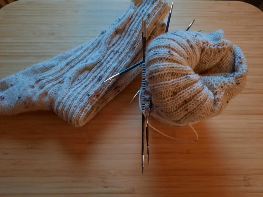 Ein fertiger naturfarbender Socken mit einem relativ groben Rippenmuster und einem seitlichen Zopf, bei dem ein Strang die gesamte Schaftlänge entlangläuft. Daneben ein angefangener Socken, dessen Schaft aufgerollt ist (um mir beim Stricken nicht im Weg zu sein).
