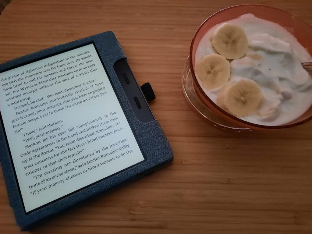 """Links der angeschaltete eReader mit einer Seite aus dem Buch """"Twelve Days of Faery"""", rechts eine kleine Glasschale mit Quark und Bananen"""
