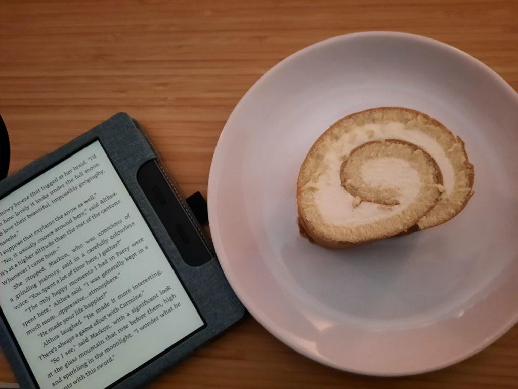 Wieder der angeschaltete eReader mit einer Seite aus meinem aktuellen Roman, rechts daneben ein weißer Teller mit einem Stück Zitronenrolle.