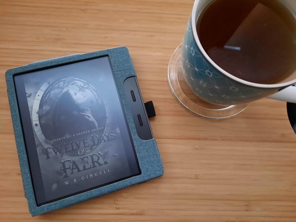 """Ein eReader, dessen Bildschirm das Cover von """"Twelve Days of Faery"""" von W. R. Gingell zeigt, daneben steht eine grüne Tasse mit Pfefferminztee"""