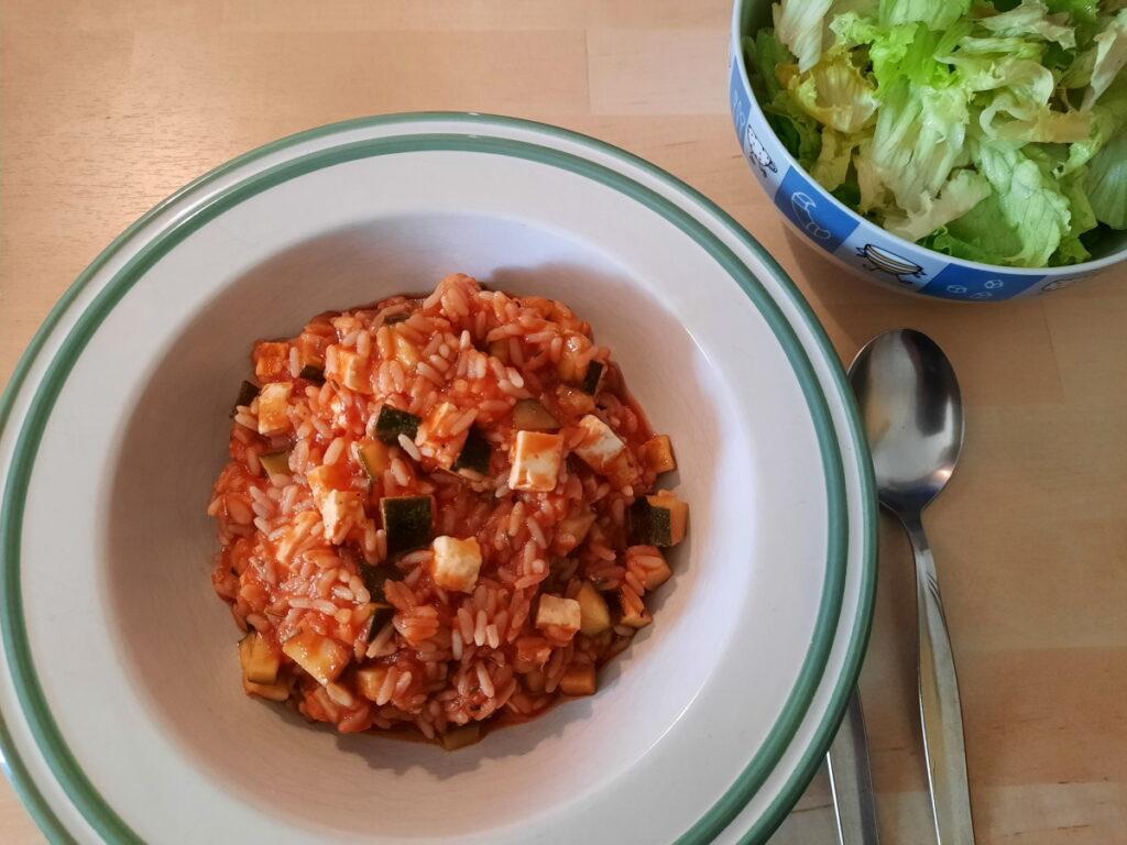 Im Vordergrund ein tiefer Teller mit einer Mischung aus Zucchini, Reis und Feta in einer Tomatensauce, im Hintergrund eine Schale mit grünem Blattsalat.