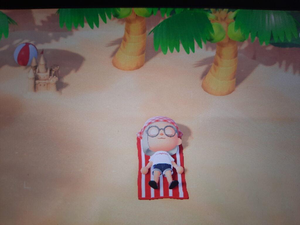 Animal-Crossing-Screenshot, der meinen Charakter in kurzer Hose und T-Shirt bekleidet auf einem Handtuch am Strand liegend zeigt. Am Kopfende sind zwei Palmen zu sehen, im Hintergrund links eine Sandburg und ein Wasserball.