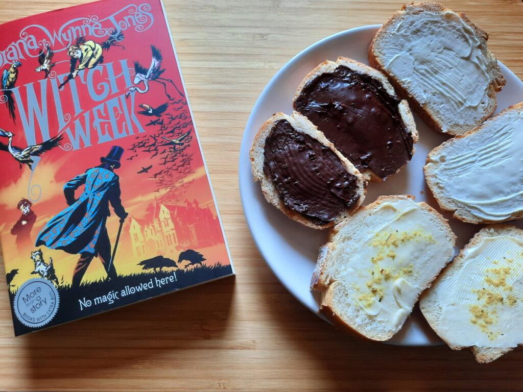 """Links noch einmal das Buch """"Witch Week"""", rechts ein weißer Teller mit sechs kleinen """"Brötchenscheiben"""", von denen je zwei mit Butter, mit Frischkäse und mit Zartbittercreme beschmiert wurden."""