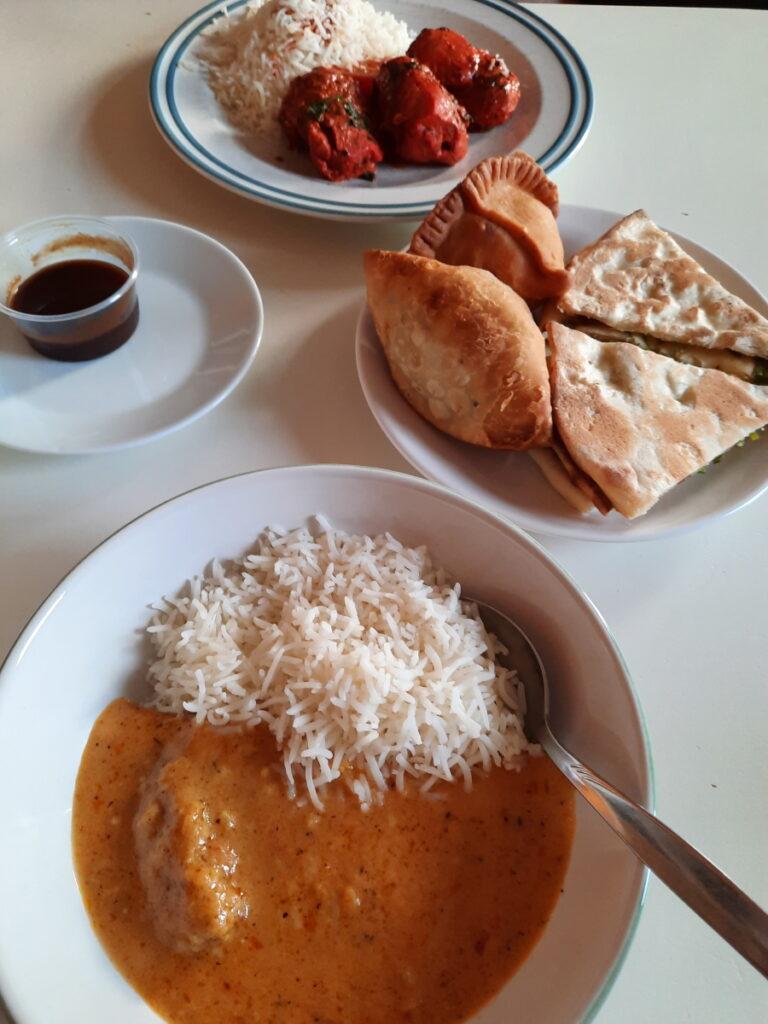 Eine Auswahl an indischen Essen. Auf einem Teller im Hintergrund kann man eine Portion Reis mit Tandoori-Chicken, in der Mitte steht ein Teller mit Samosas und Naan, links davon ein Schälchen mit Tamarindsauce und in einer Schale im Vordergrund sieht man Reis mit Mandel-Curry.